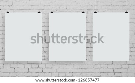 brick wall with three white poster