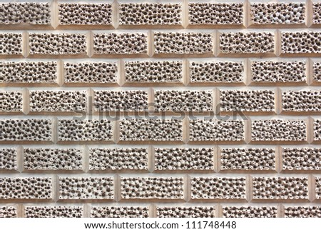 Brick Wall with unusual texture made up of small holes - stock photo