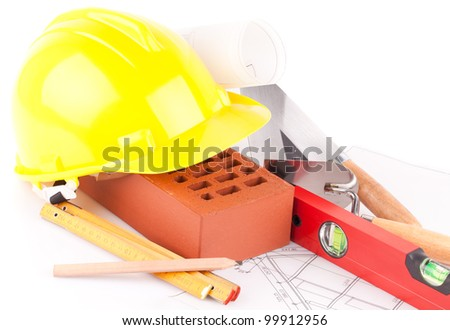 brick, yellow hard hat, tools and construction plans  isolated on white background