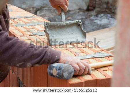 bricklayer builds a wall #1365525212