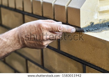 Bricklayer builds new fence from facing bricks. Alignment of inter-brick joints #1583011942