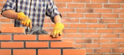 Bricklayer industrial worker installing brick masonry
