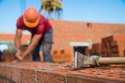 Bricklayer worker installing brick masonry on exterior wall. Professional construction worker laying bricks.
