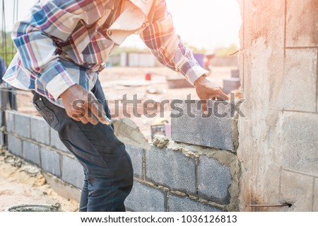 Bricklayer working with bricks for building a wall, Construction tools