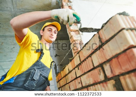 bricklaying. Construction worker building a brick wall #1122372533
