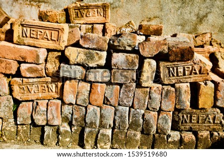 Bricks pile close up view. Old Bricks Texture. Orange and Yellow antique Bricks pattern. Construction industry raw materials. Building materials. Vintage Bricks pile from Nepal. Abstract backgrounds.