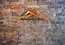 Bricks wall background with rack and wooden clothes hangers, cafe restaurant wardrobe corner, loft style