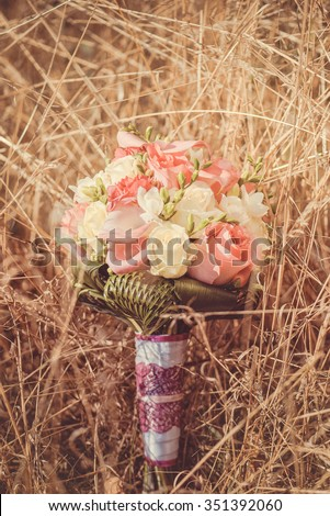 Bridal autumn bouquet with red and white roses over yellow autumn grass. Wedding in fall.