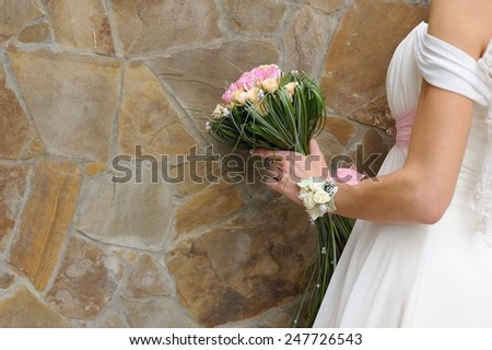 Bridal Bouquet Against Wall; a bride holding her bridal bouquet at a decorated wall