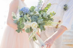 Bridal bouquet in white and blue colors in the hands of the bride and groom
