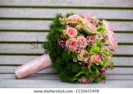 Bridal bouquet lies on a white bench, beautiful flowers,wedding bridal bouquet,the bride's bouquet, bridal bouquet,Bouquet of flowers. Bridal bouquet. Floristics. Wedding bouquet from different colors #1150655498