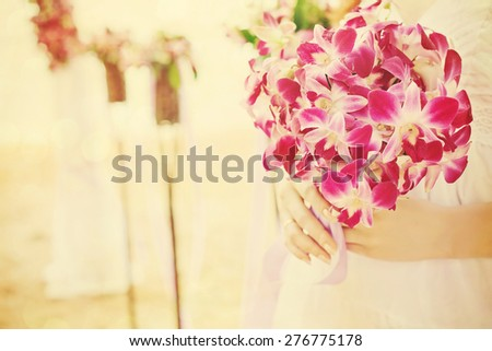bridal bouquet of orchids in Bride hands on the wedding ceremony by the sea