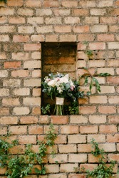 bridal bouquet of pink and white peonies, roses, branches of eucalyptus tree, veronica, matthiola and white ribbons in a niche of a brick wall
