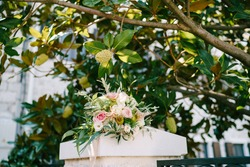 bridal bouquet of white and pink roses, branches of eucalypt tree, astilbe, ammi, small green pomegranates and pink ribbons on the fence under magnolia tree