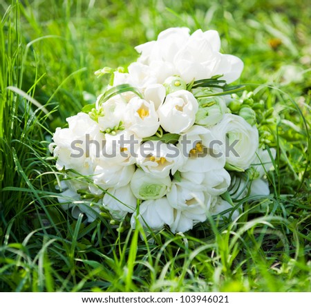 bridal bouquet of white flowers the bride's on the green grass