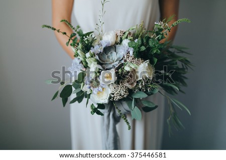 Bridal bouquet. Wedding. The girl in a white dress standing on a gray background and holds a beautiful bouquet of white, blue, pink flowers and greenery, decorated with long silk ribbon