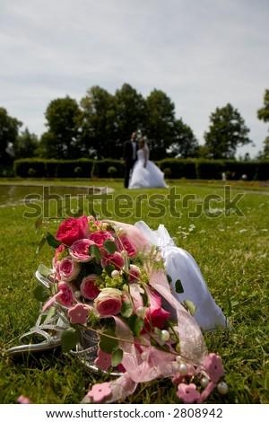 Bridal Bouquet with her shoes on meadow in a park. Bridal couple in the distance and diffuse. Focus on flowers.