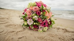 bridal bouquet with pink flowers at the beach