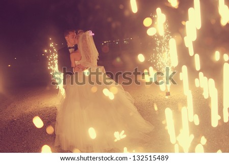 Bridal couple dancing sorrounding by fireworks