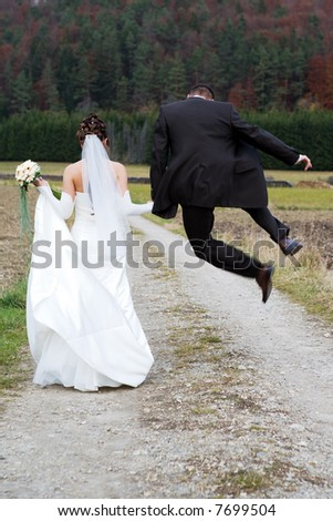 Bridal couple from behind. He makes a dido. Autumn. - stock photo