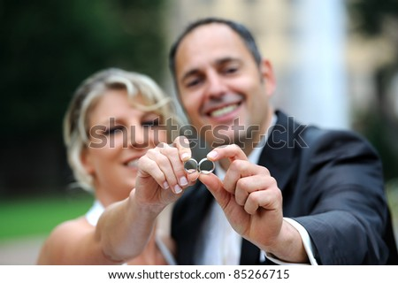 bridal couple is showing the rings