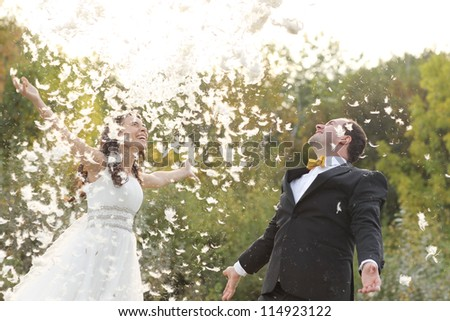 bridal couple playing with feathers