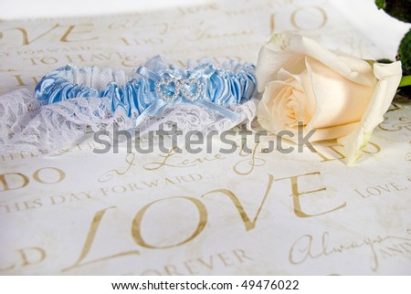 bridal garter with rose on wedding paper