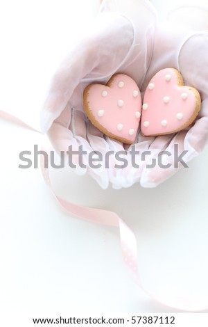 Bridal hands you a pink icing heart cookies - stock photo