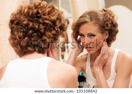 Bridal preparation. Woman with evening hairstyle looking into a mirror