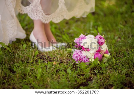 Bridal shoes and bouquet on the grass #352201709