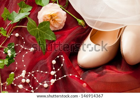 bridal shoes on red tulle white white pearls and a rose besides