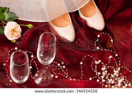 bridal shoes on red tulle white white pearls and two champagne glasses