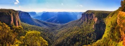 Bridal vale waterfall from Govett leap lookout towards Pulpit rock and surrounding sandstone mountain ranges in Blue Mountains on a sunny morning.