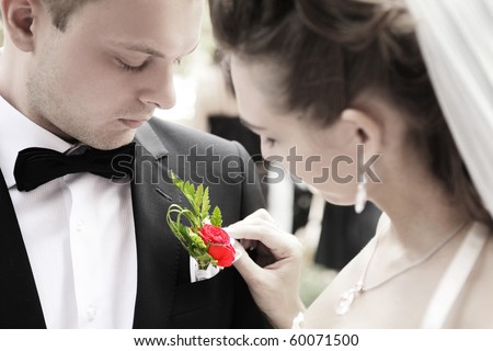 bride adjusting flower on groom's jacket