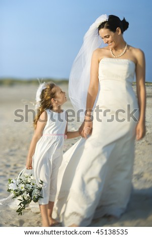 Bride and a flower girl hold hands on a sandy beach. Horizontal shot.