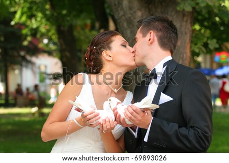 Bride and Bridegroom are kissing, they have pigeons