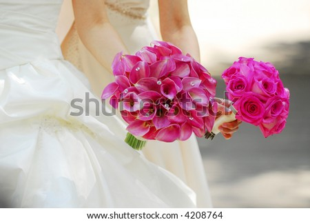 Bride and bridesmaid holding bouquets of pink flowers