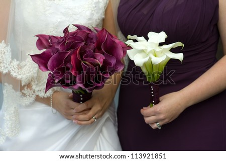 bride and bridesmaid holding bouquets of wedding flowers