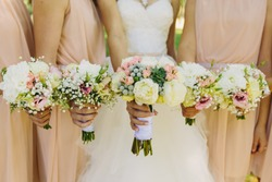 Bride and bridesmaids hand with beautiful flowers