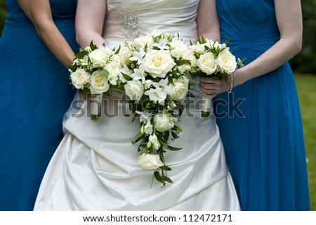 bride and bridesmaids holding wedding bouquets of white roses
