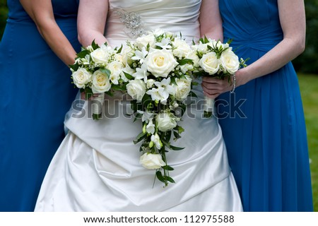 bride and bridesmaids in blue holding wedding bouquets