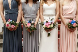 Bride and bridesmaids in pastel dresses stand in a ray with wedding bouquets