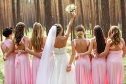 Bride and bridesmaids in pink dresses having fun at wedding day. Happy marriage and wedding party concept
