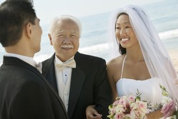 Bride and father with groom at beach wedding