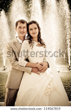 bride and groom against the fountain