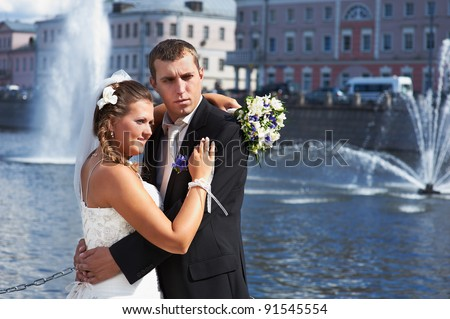 Bride and groom and fountains in river on wedding walk
