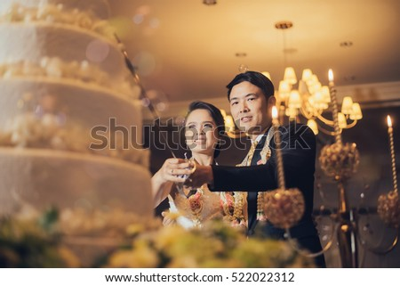 Bride and groom are cutting cake for celebration on their wedding day #522022312