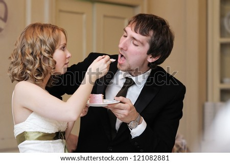 Bride and groom are eating their wedding cake