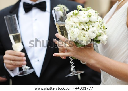Bride and groom are holding champagne glasses - stock photo
