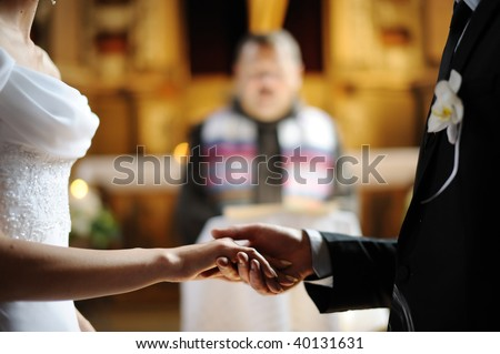 and groom are holding each other 39s hands during church wedding ceremony